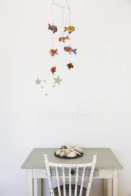 Fish mobile decoration hanging over desk — Stock Photo
