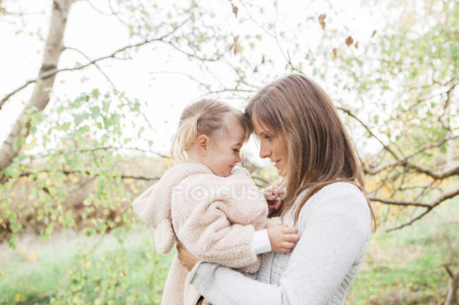 Affectionate mother holding toddler daughter in park — Stock Photo