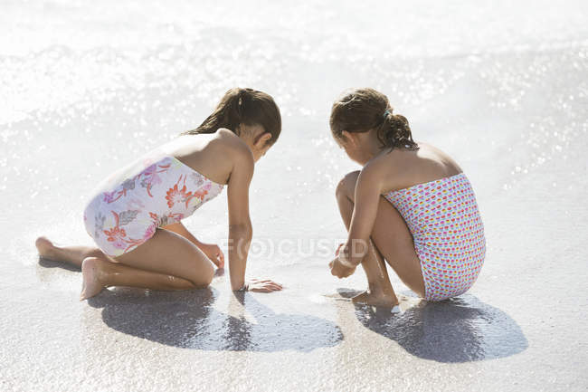 Девушки играют вместе в серфинге на пляже — стоковое фото