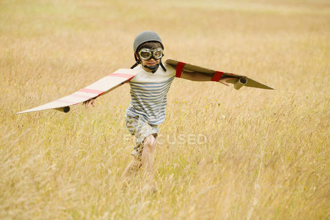 Boy running with wings and aviators cap and flying goggles in field — Stock Photo