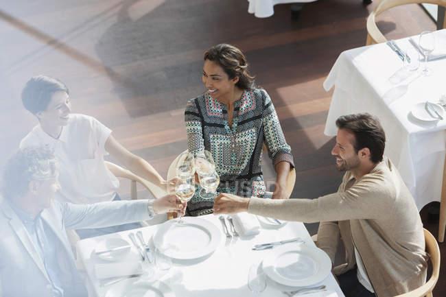 Amigos brindando com taças de vinho na mesa do restaurante — Fotografia de Stock