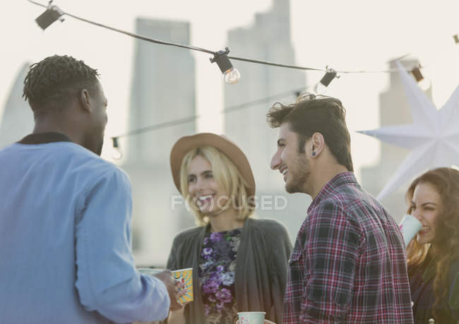 Young adult friends talking and drinking at rooftop party — Stockfoto
