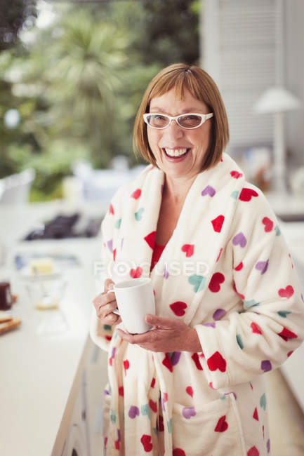 Portrait smiling mature woman drinking coffee in bathrobe — Stockfoto