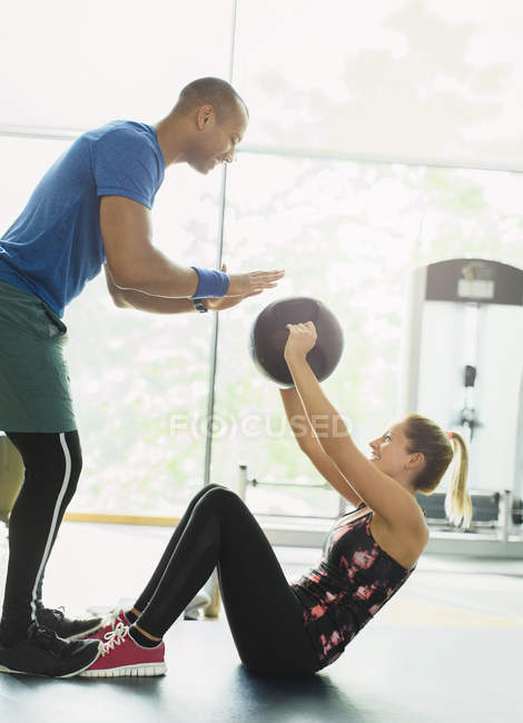 Personal trainer guiding woman with medicine ball at gym — Stock Photo