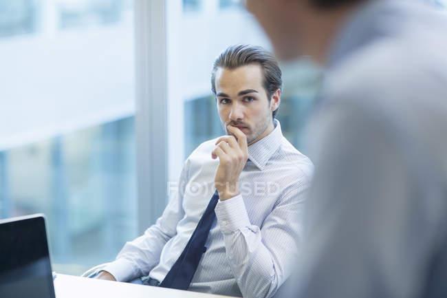 Uomini d'affari che parlano in ufficio mentre siedono a tavola — Foto stock