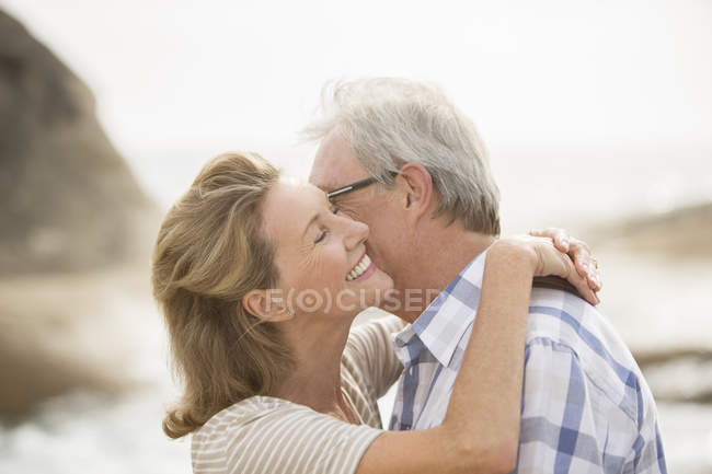 Older couple kissing on beach — Stock Photo