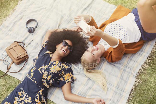 Amis prendre selfie détente sur couverture dans l'herbe — Photo de stock