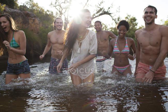 Amis pataugeant dans la rivière pendant la journée — Photo de stock