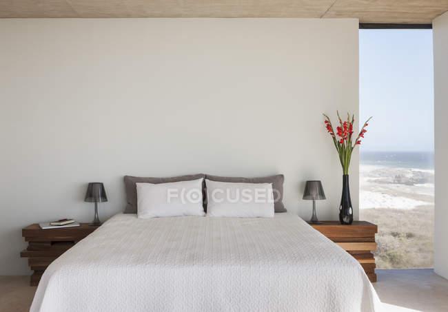 Vaso de flores ao lado da cama em quarto com vista para o mar — Fotografia de Stock