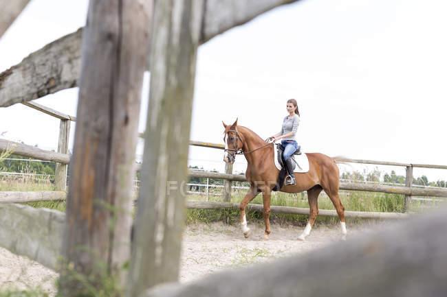 Frau Reiten in ländlichen eingezäunten Weide — Stockfoto