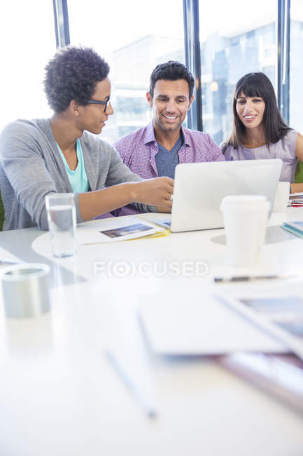 Business people sharing laptop in meeting — Stock Photo