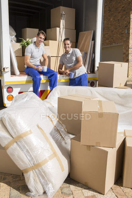 Movers sitting in moving van in driveway — Stock Photo