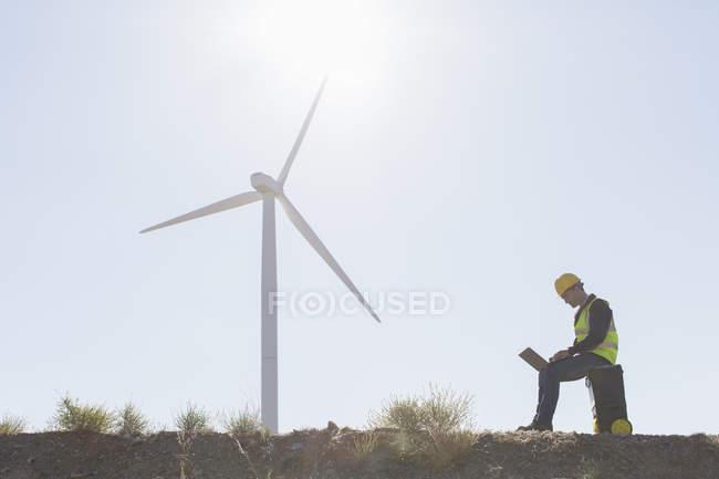 Travailleur utilisant un ordinateur portable par éolienne dans le paysage rural — Photo de stock