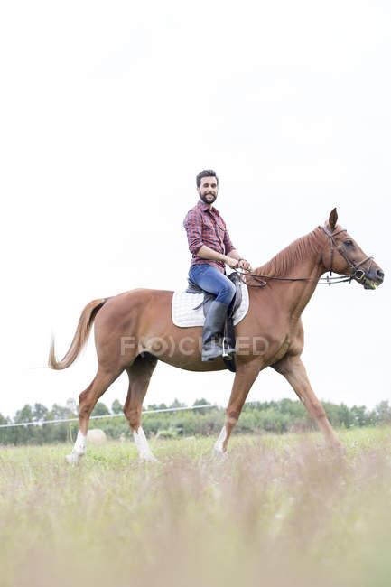 Retrato sorridente homem cavalgando no campo rural — Fotografia de Stock