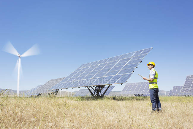 Worker examining solar panels in rural landscape — Stock Photo