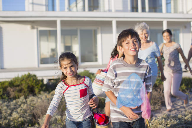 Multi-generation family on beach path outside house — Stock Photo