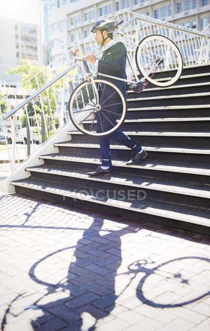 Бізнесмен в костюмі і шолом, несучи велосипеді вниз по сходах міських — стокове фото
