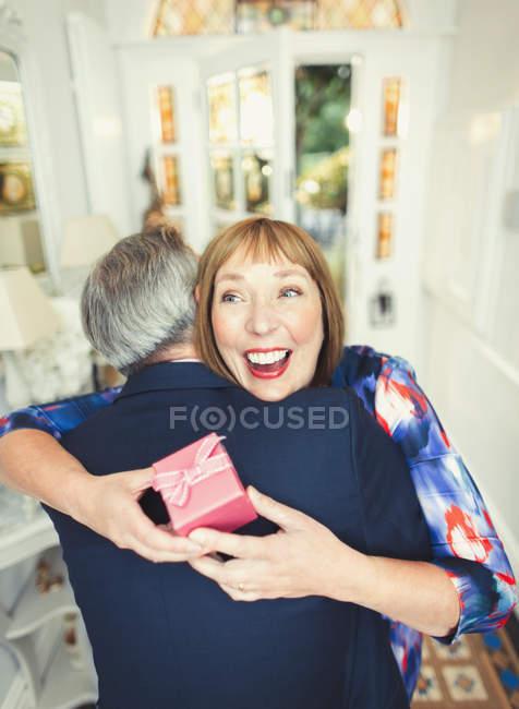 Mujer madura sorpresa recibir regalo de marido - foto de stock