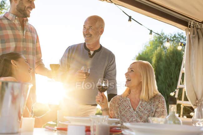 Famiglia bere vino al tavolo soleggiato patio — Foto stock