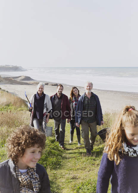 Multi-generation family walking on sunny grass beach path — Stock Photo