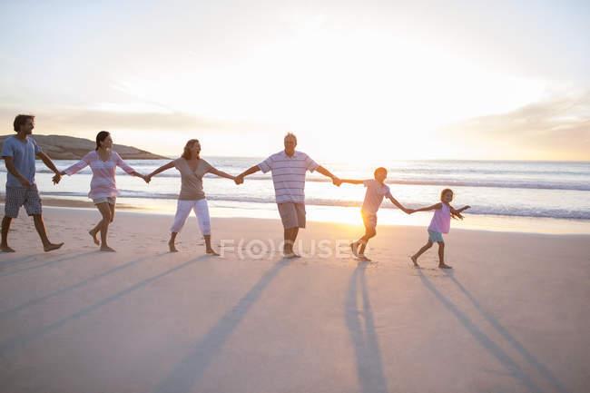 Familie hält Händchen am Strand — Stockfoto