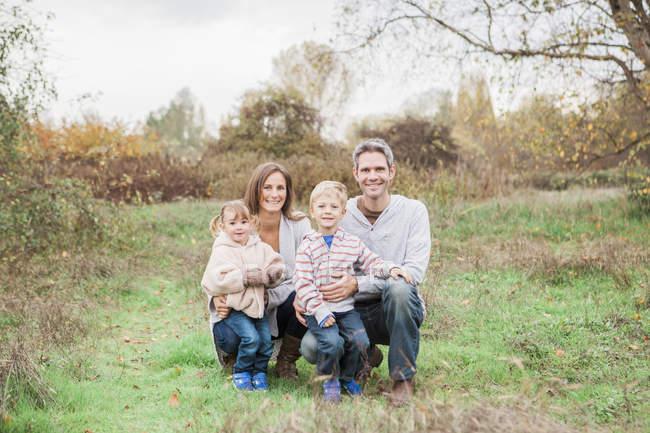 Portrait famille souriante dans le parc rural — Photo de stock