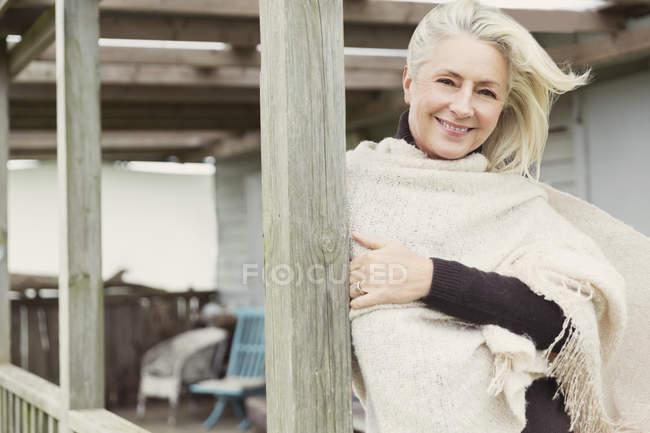 Ritratto donna anziana sorridente che indossa scialle sul portico ventoso — Foto stock