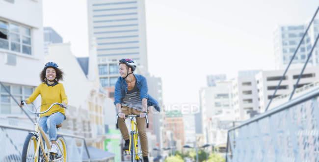 Amis avec des casques d'équitation vélos sur passerelle urbaine — Photo de stock