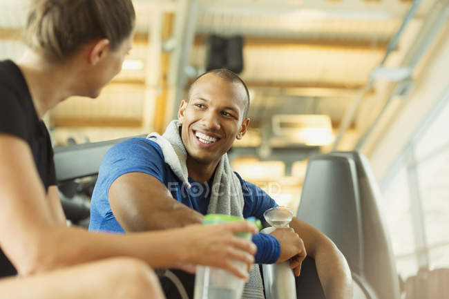 Smiling man and woman talking at gym — Stockfoto