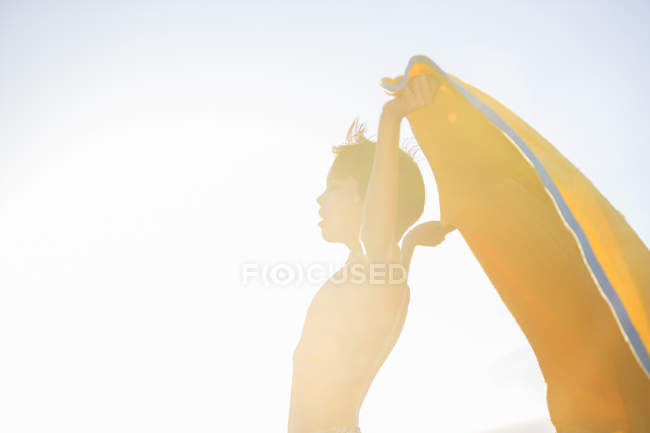 Boy playing with towel on beach — Stock Photo