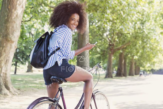 Портрет посміхаючись жінка велосипед їзда з mp3-плеєр і навушники в парку — стокове фото