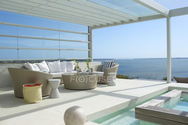 Диван і крісла біля плавального басейну з видом на океан — стокове фото