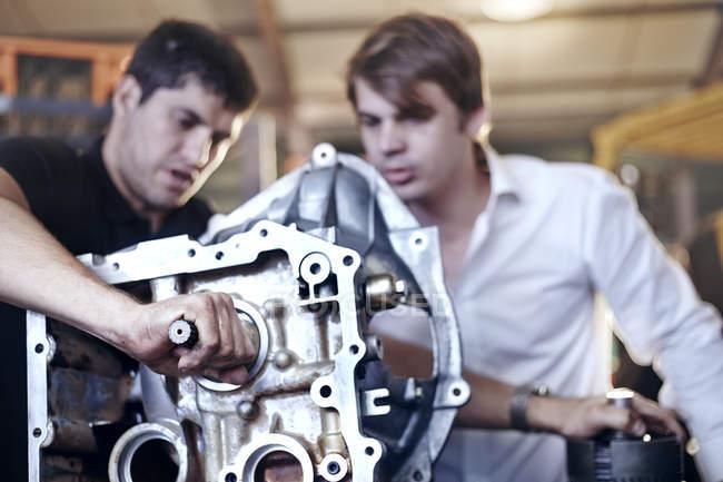 Mécanique examinant la partie dans l'atelier de réparation automobile — Photo de stock