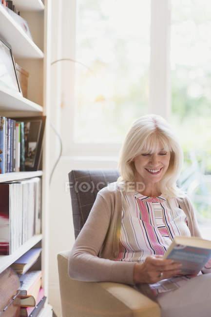 Smiling senior woman reading book in den — Stockfoto