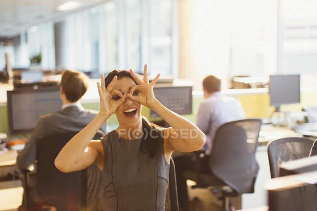 Ritratto di donna d'affari giocosa che finge di indossare occhiali in ufficio — Foto stock