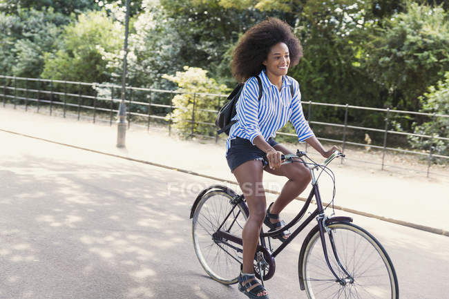 Woman with afro riding bicycle in park — Stock Photo