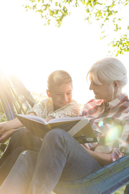 Grandmother reading to grandson in sunny hammock — Stock Photo