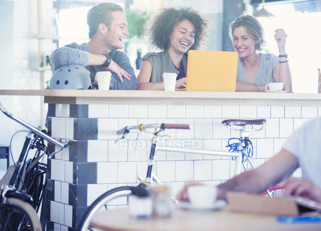 Friends sharing laptop at cafe bar — Stock Photo