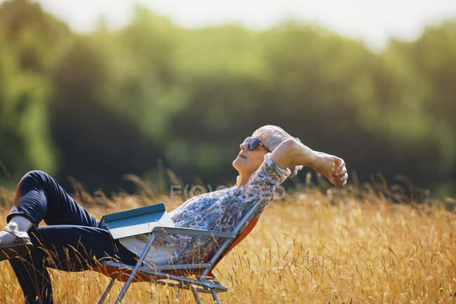 Mulher sênior despreocupada relaxante com livro no campo ensolarado — Fotografia de Stock