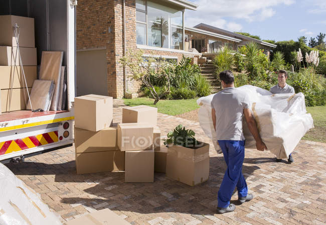 Movers carrying sofa from moving van to house — Stock Photo