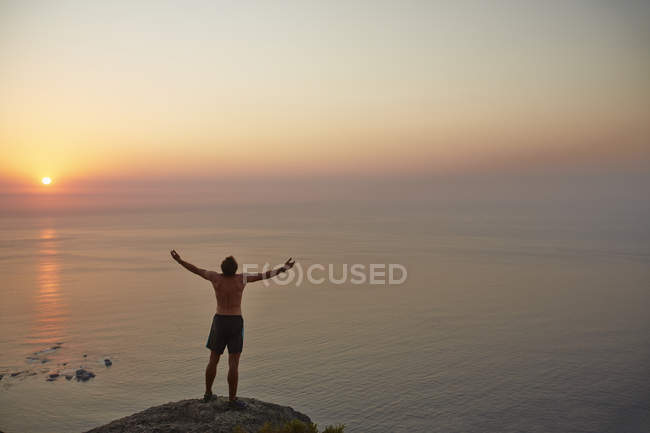 Exuberant male runner with arms outstretched on rock overlooking ocean sunset — Stock Photo