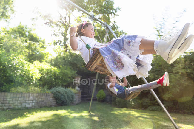 Carefree girls swinging in backyard — Stock Photo