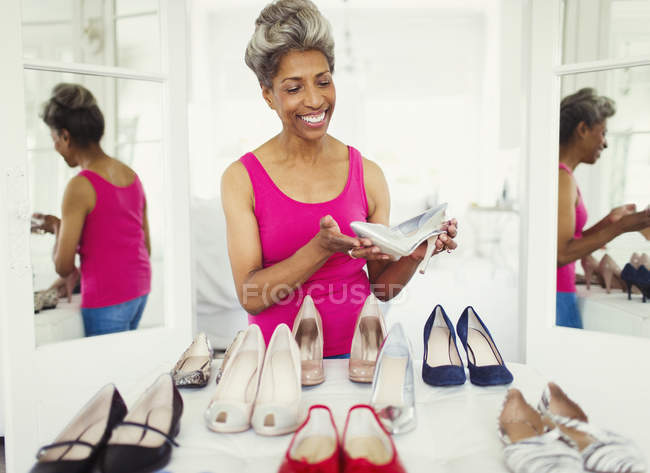 Smiling mature woman looking at high heels in closet — Stockfoto