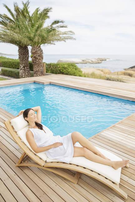 Женщина отдыхает у бассейна в дневное время — стоковое фото