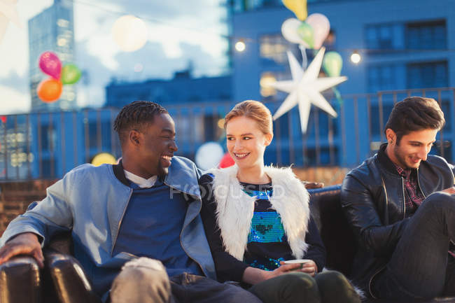Young man and woman flirting at nighttime rooftop party — Stockfoto