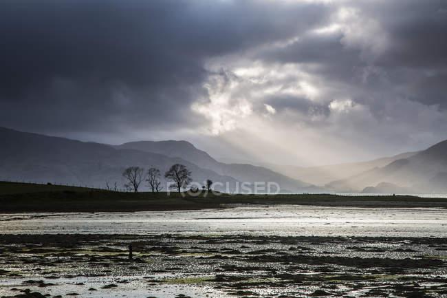 Raios de sol em um céu tempestuoso sobre Lago, Escócia — Fotografia de Stock