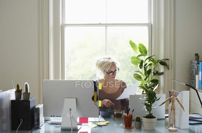 Молодая женщина читает документы на столе в домашнем офисе — стоковое фото