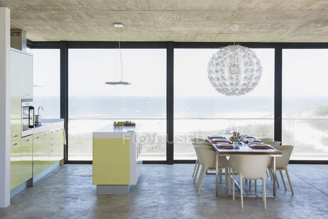 Modern dining room and kitchen overlooking ocean — Stock Photo