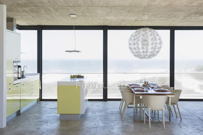 Современная столовая и кухня с видом на океан — стоковое фото