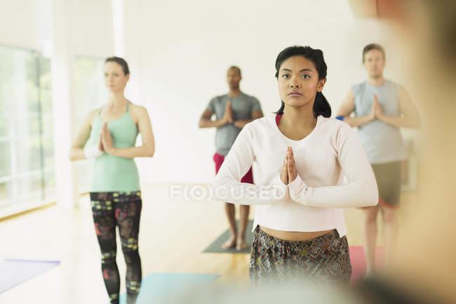 Focalizzato la donna con le mani in posizione di preghiera in classe di yoga — Foto stock